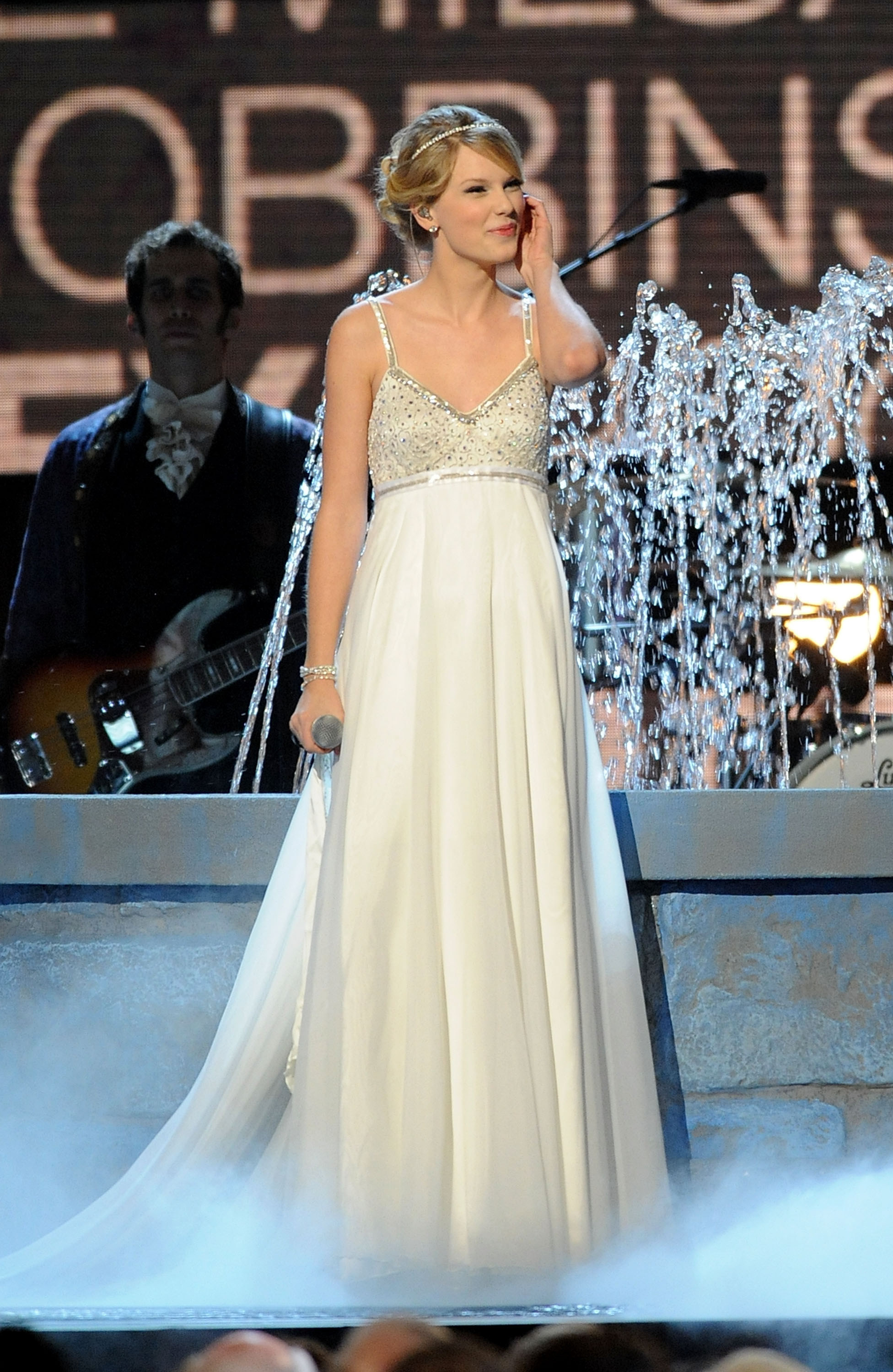 Taylor Swift in a long white gown performing Love Story
