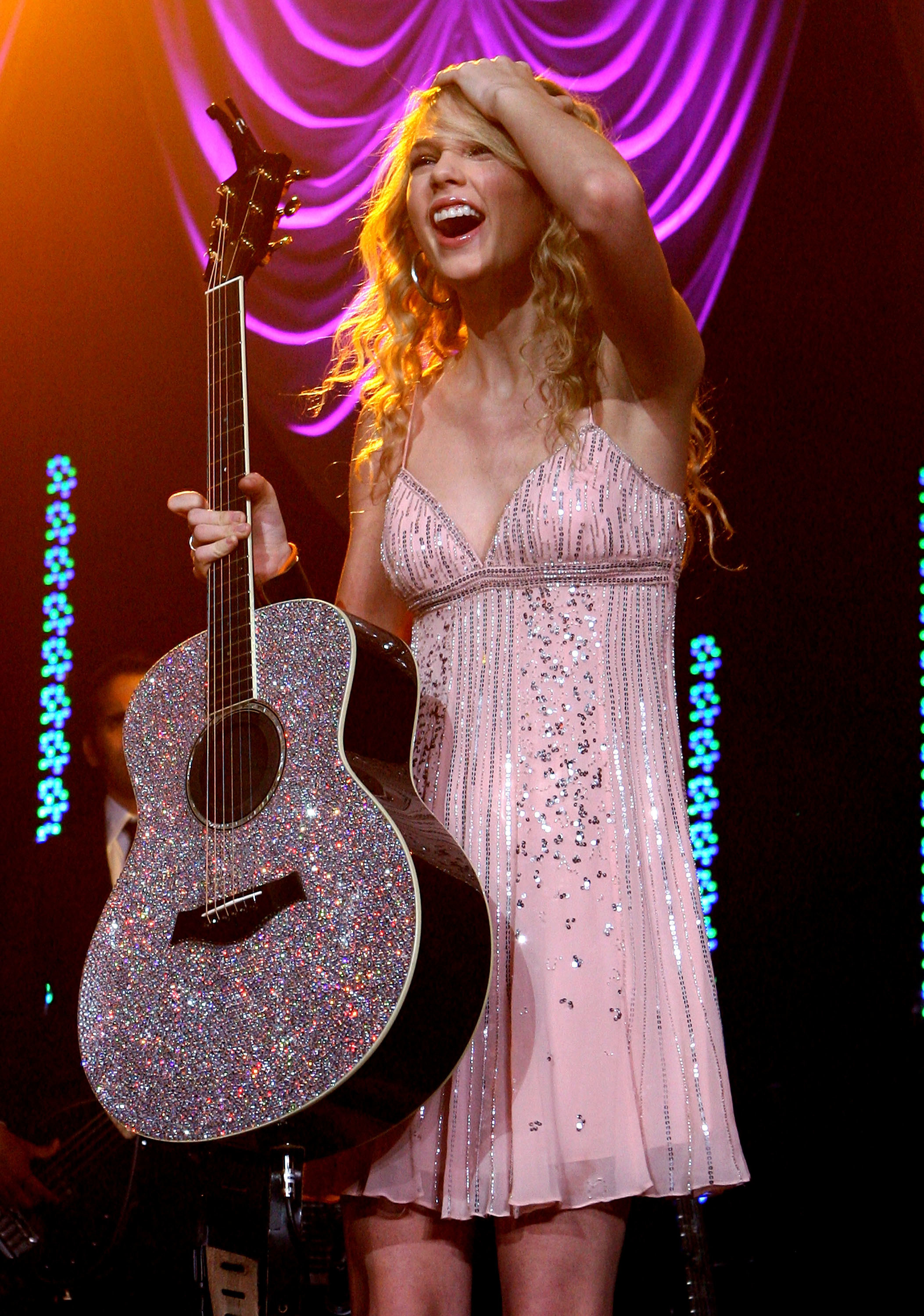 Taylor Swift performing in a pink dress, holding glittery guitar