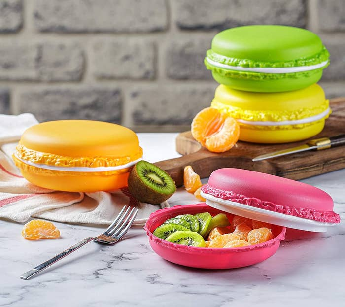 four macaron-shaped containers in orange, yellow, green, and pink