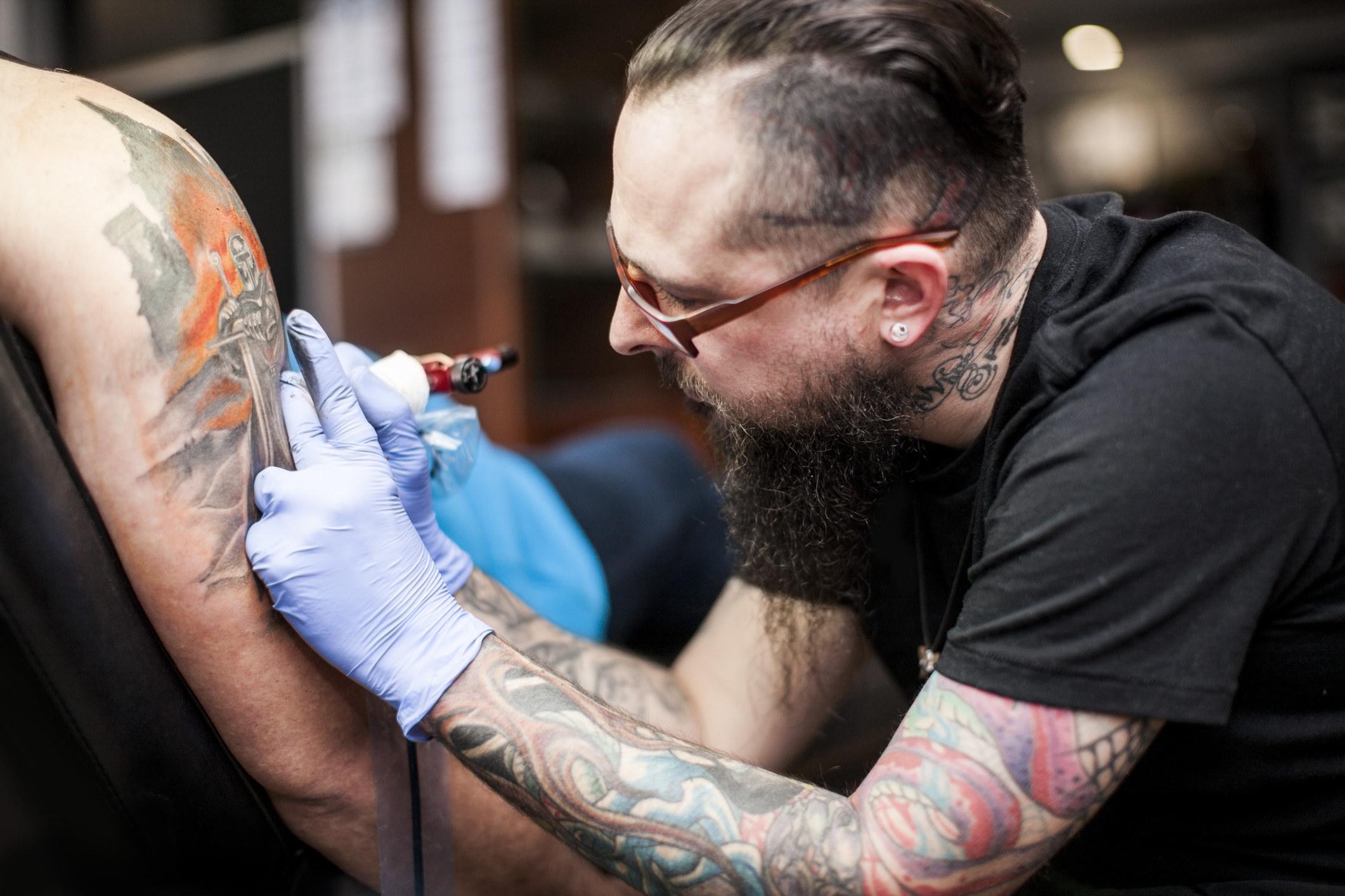 a tattoo artist working on an arm