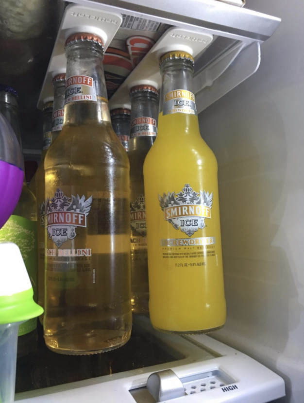 two wine coolers in bottles hanging from a magnet in the fridge
