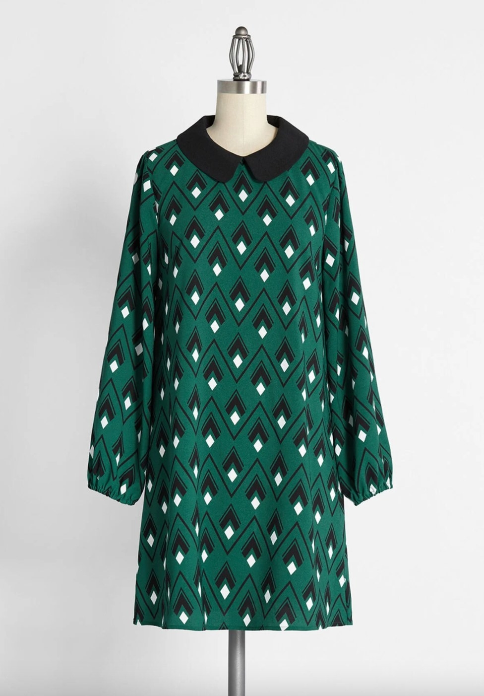 The long-sleeved shift dress in green geometric pattern with a black peter pan collar