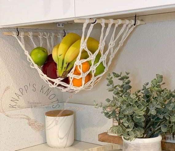 a macrame hammock hanging from underneath a kitchen cabinet with fruits in it