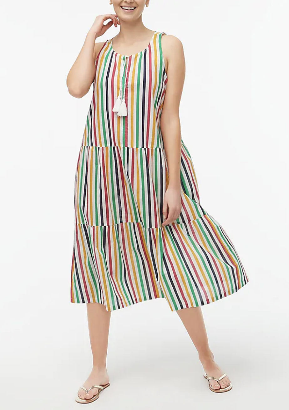 Model in a flowing rainbow and white striped tiered midi dress with tassels at the collar