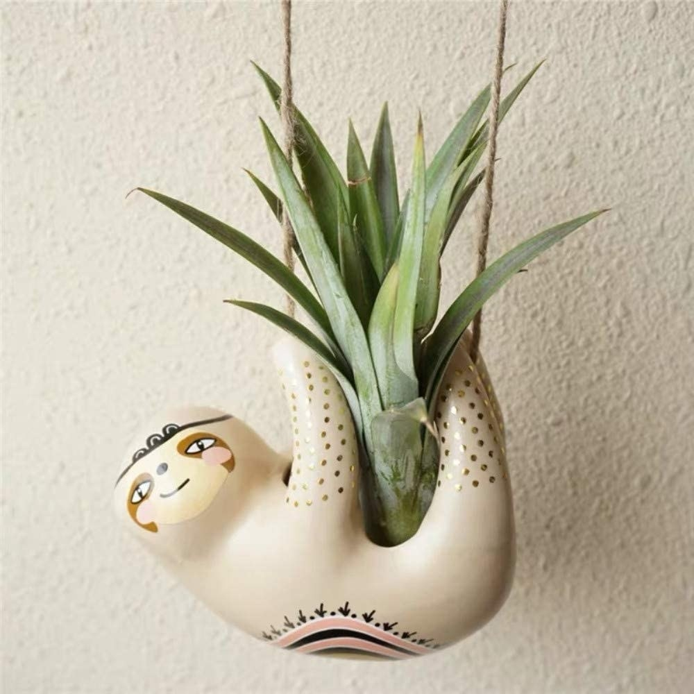 Hanging sloth planter with plant in its belly