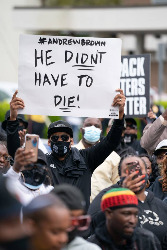 "A man holds up a protest sign in a crowd reading ""Hashtag Andrew Brown / He didn't have to die"""