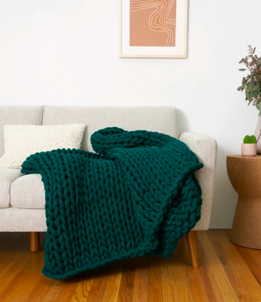 the plant-based weighted blanket in a deep green color on a couch