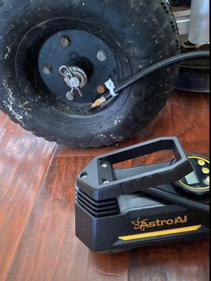 A reviewer's portable air pump plugged into a tire