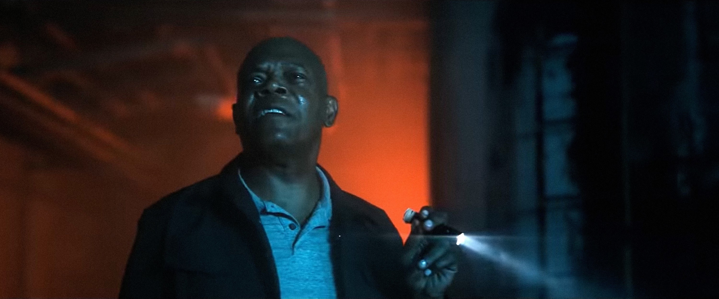 Samuel L. Jackson using a flashlight while looking ahead