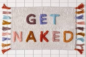 "A colorful bath mat with the words ""Get Naked"" and tassels on two sides"