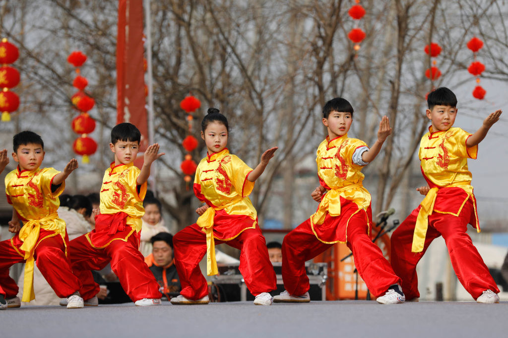 Chinese children in traditional gowns perform karate