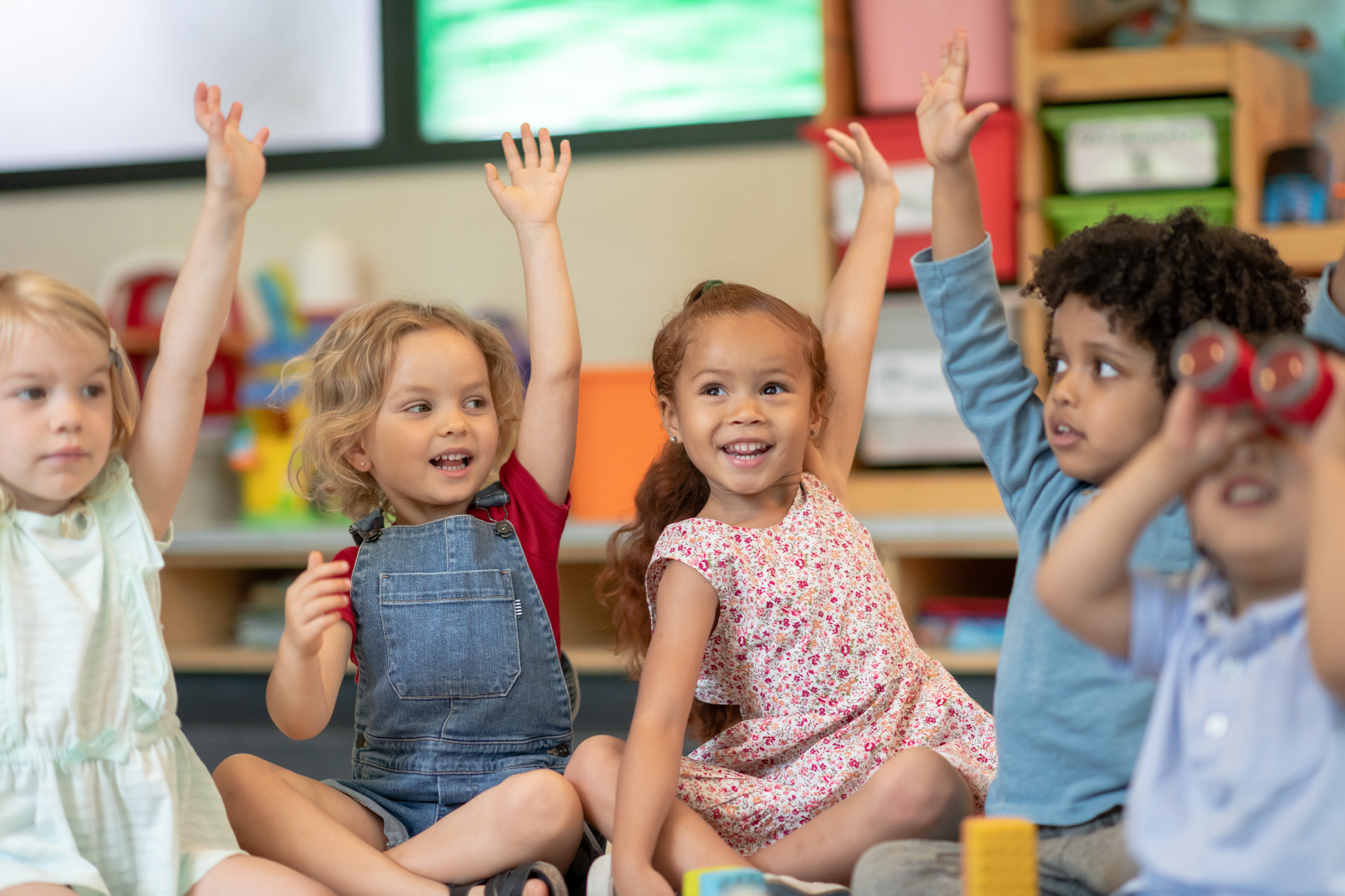 Multicultural children smile and raise hands in a classroom
