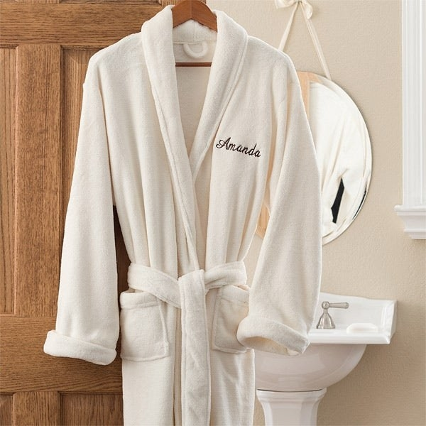 """a white robe that sys 'Amanda"""" hanging on a doorway"""
