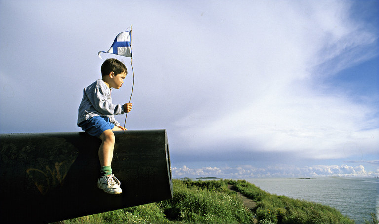 A boy on a mountaintop holds a Finnish flag