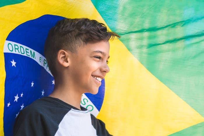 A boy smiles in front of the Brazilian flag