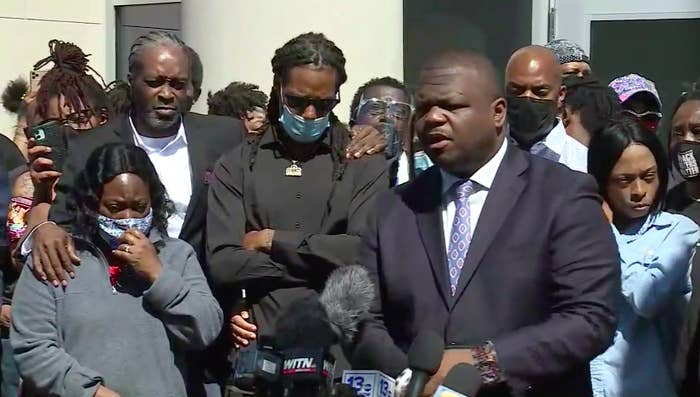 A group of Black people, frowning, grieving, and their arms crossed, stand around news station microphones