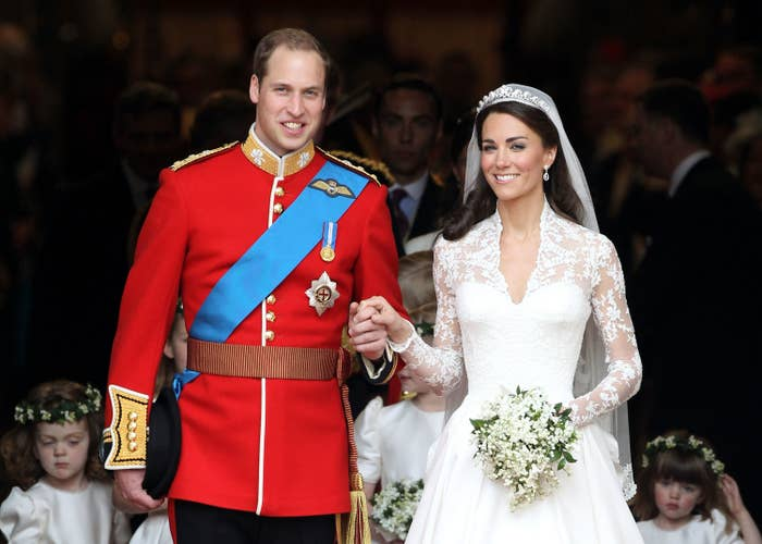 Prince William in a military uniform and Kate Middleton in a wedding dress holding hands and smiling at the camera