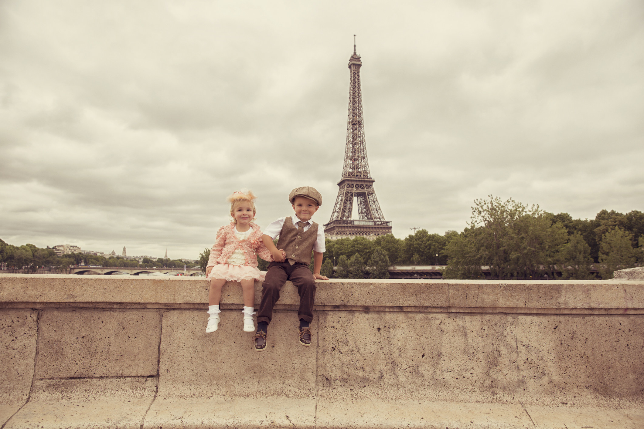 A small boy and girl are dressed in old-timey clothes as they stand in front of the Eiffel Tower
