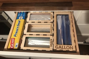 open kitchen drawer with sections for different sized plastic bags