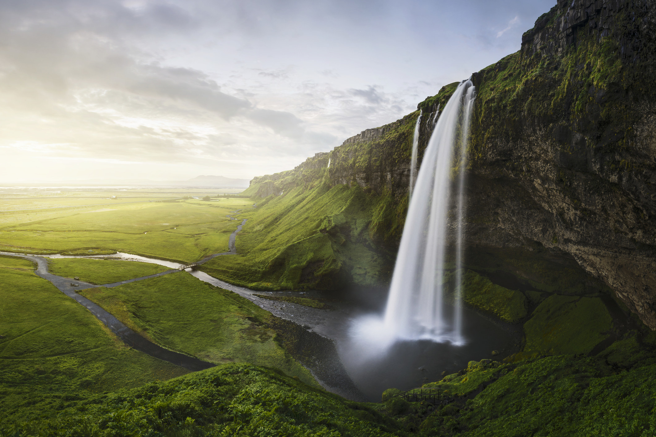A waterfall surrounded by lush green landscape in Iceland.