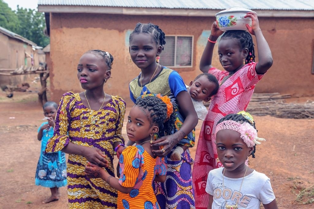 Girls in bright colored clothes hang out together outside a home in ghana
