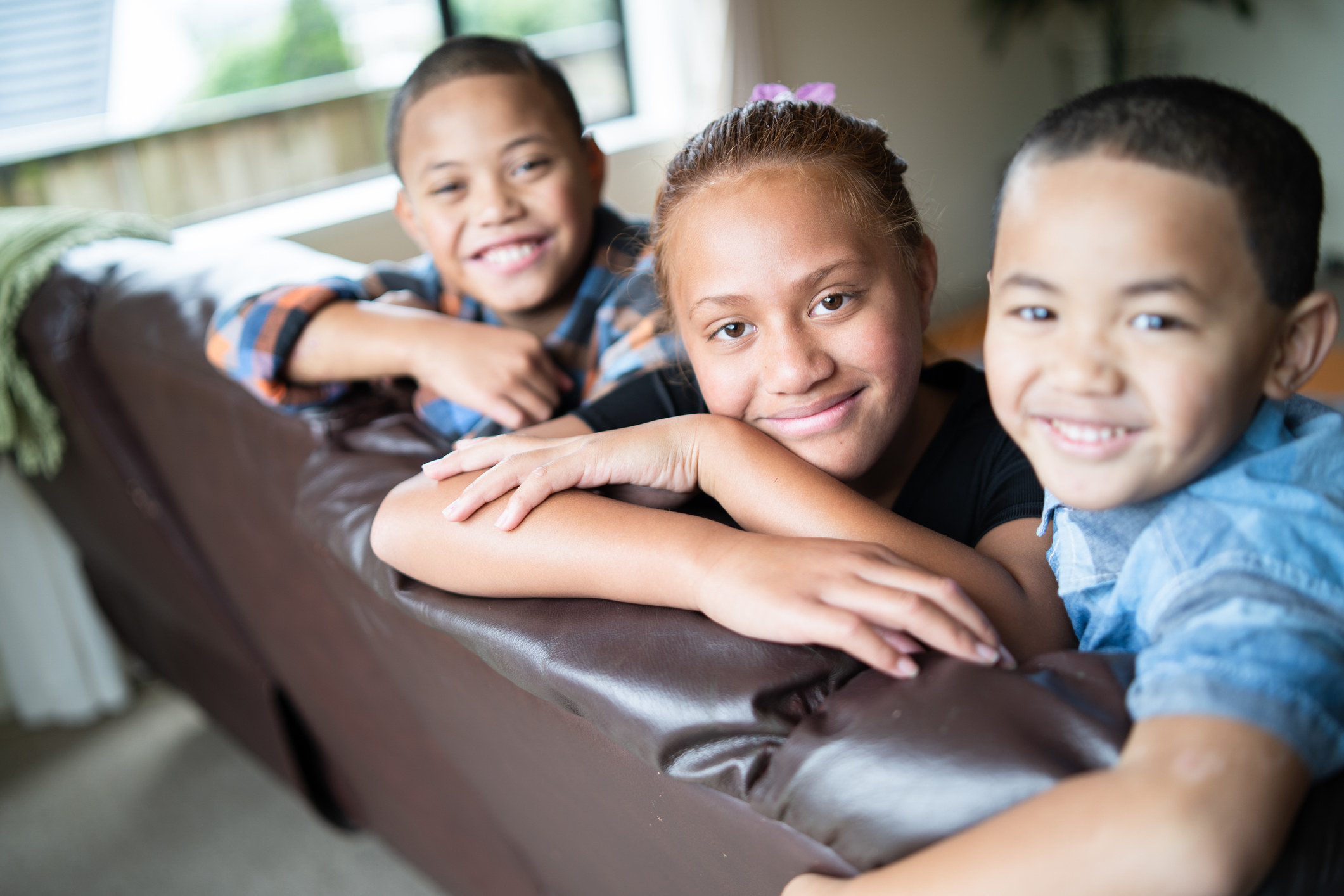 Maori children smile on a couch