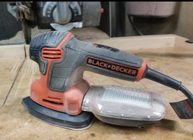 A reviewer's electric sander on a plank of wood