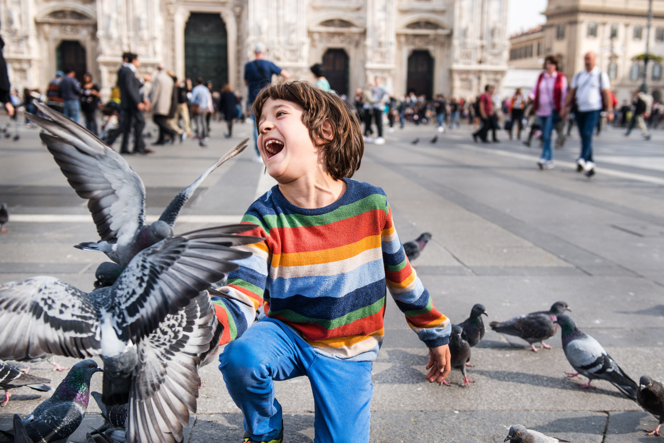 A boy laughs as he's surrounded by pigeons in Venice