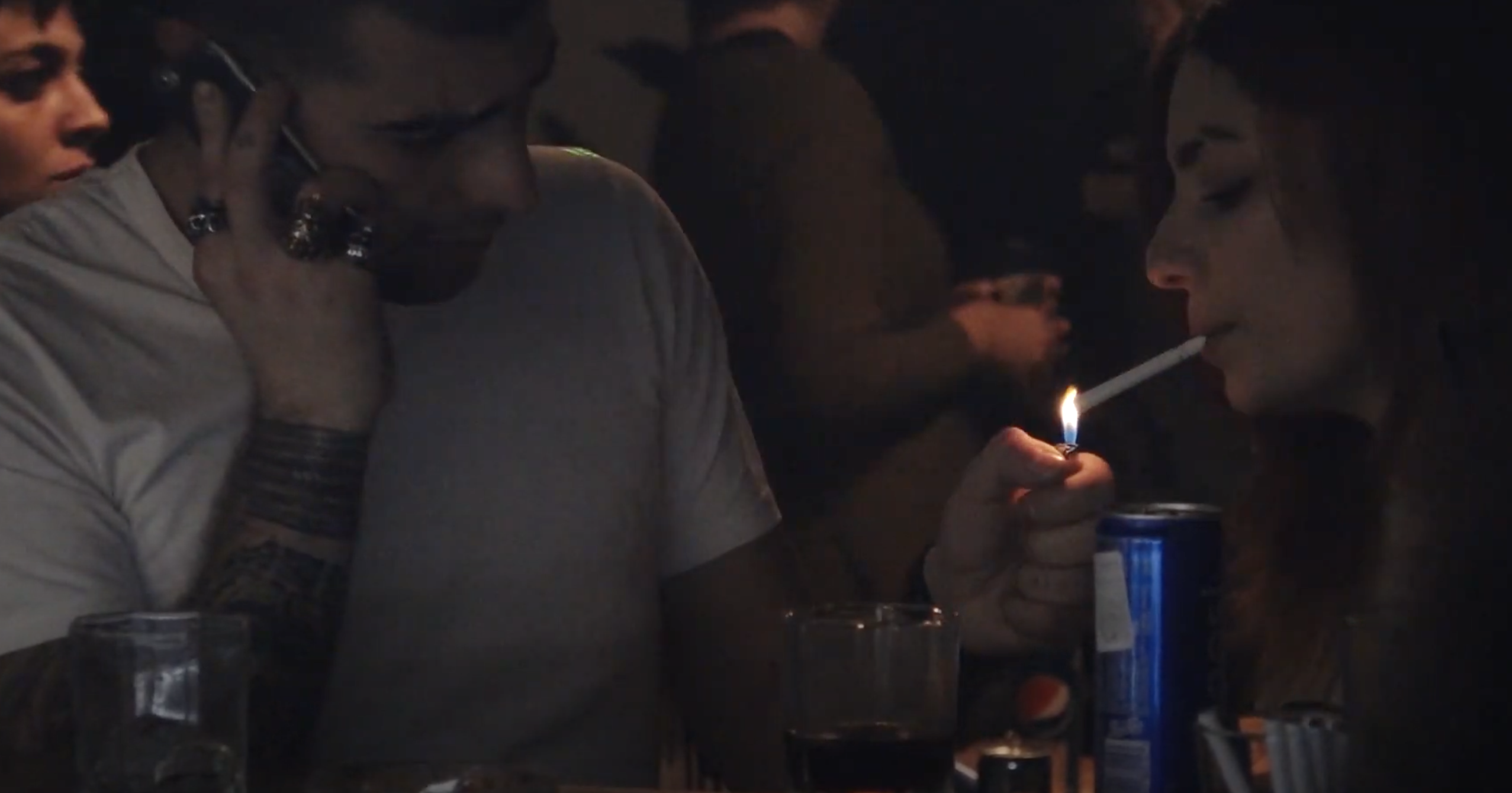 Someone gives their friend a light for their cigarette