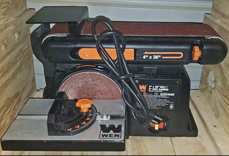 A reviewer's electric sander in their workspace