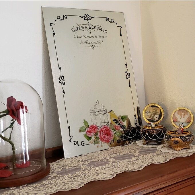 The mirror on a shelf with two music boxes and a rose in a glass case