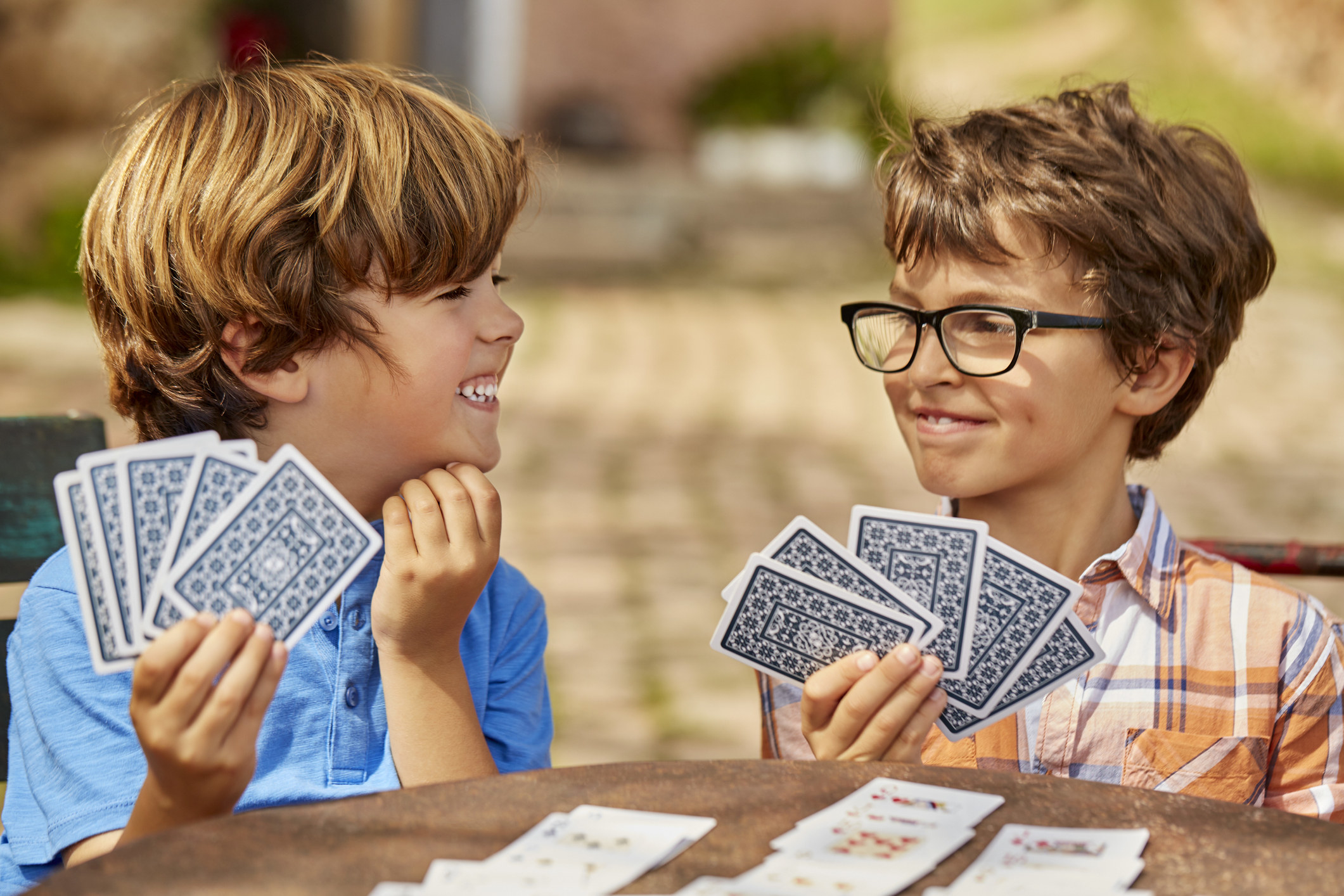Two Spanish boys laugh as they play cards