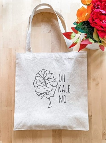 """The tote bag which reads """"oh kale no"""" with an illustration of a smiley faced kale"""