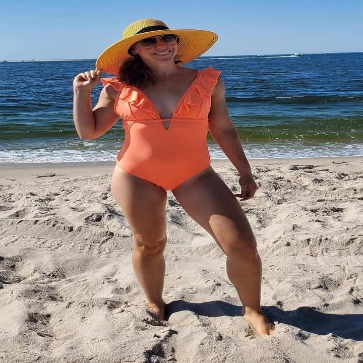 reviewer wearing the plunging keyhole suit with ruffled straps in orange