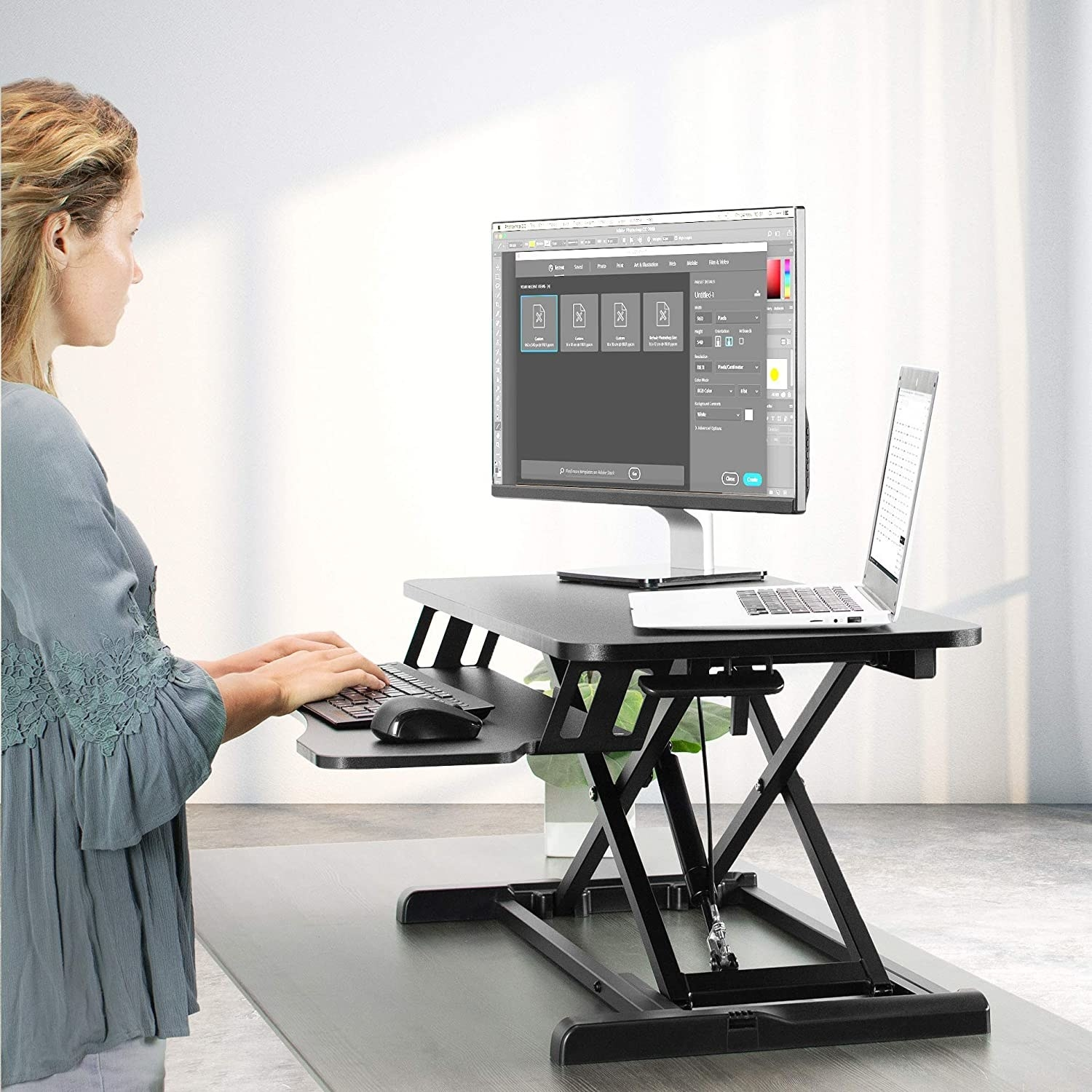 A person standing to use their computer which is placed on top of the standing desk attachment