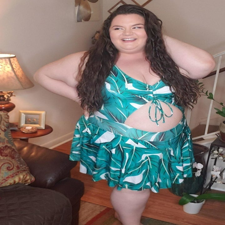 reviewer wearing the palm leaf-print swimdress with a V-neck and cutout at the stomach