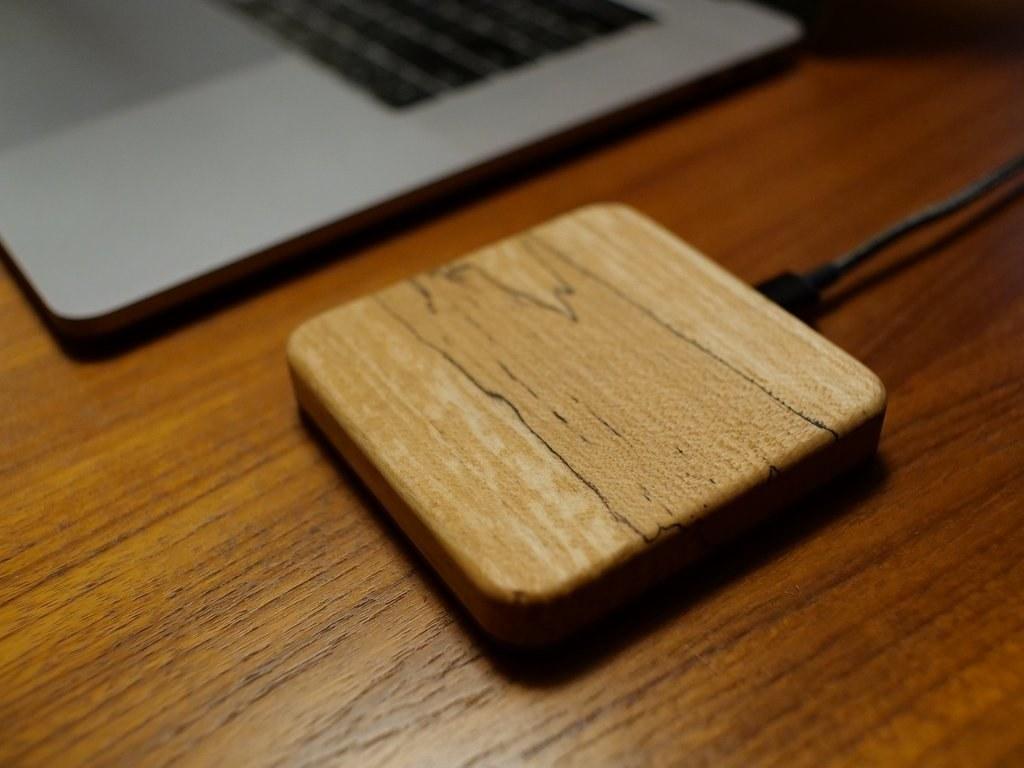 a wooden charger attached to a computer via a USB cable