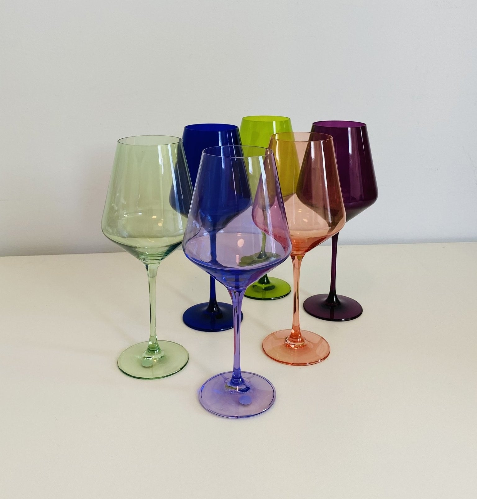 six glasses in pink, green, purple, lime, dark purple, and dark blue