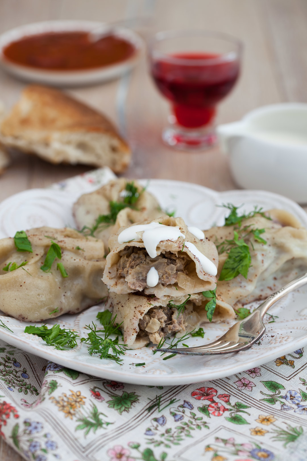 A plate of manti garnished with fresh herbs