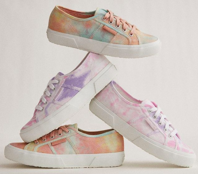 Two pairs of the 2750 Fantasy Cotu sneakers in purple and pastel stacked on top of each other