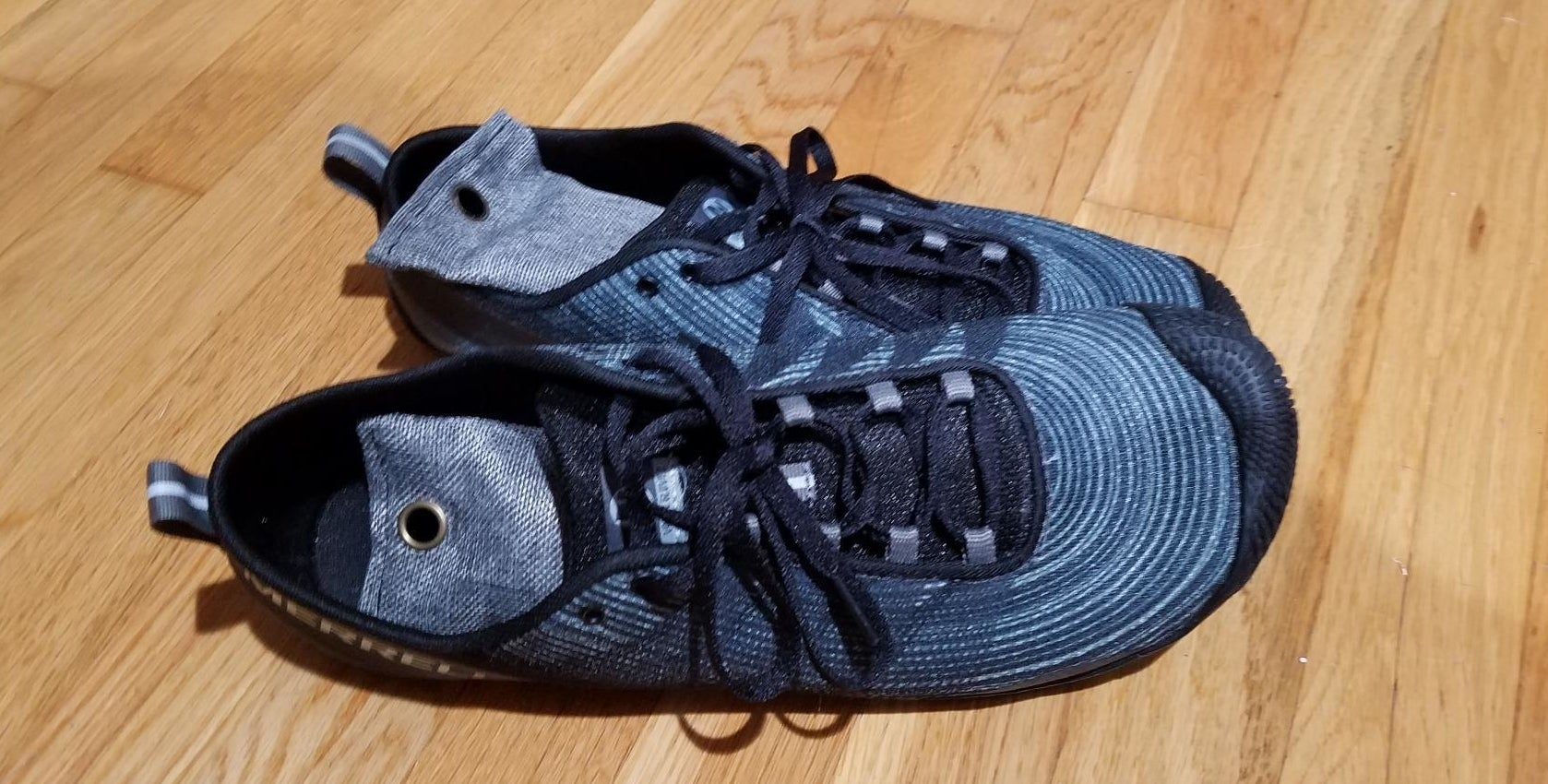 a reviewer photo of a pair of sneakers with dark blue shoe deodorizers inside