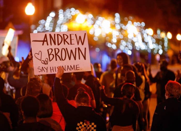 """A demonstrator in a crowd holds up a sign that says """"Andrew Brown, say his name"""" and has small drawings of a heart and a broken heart"""