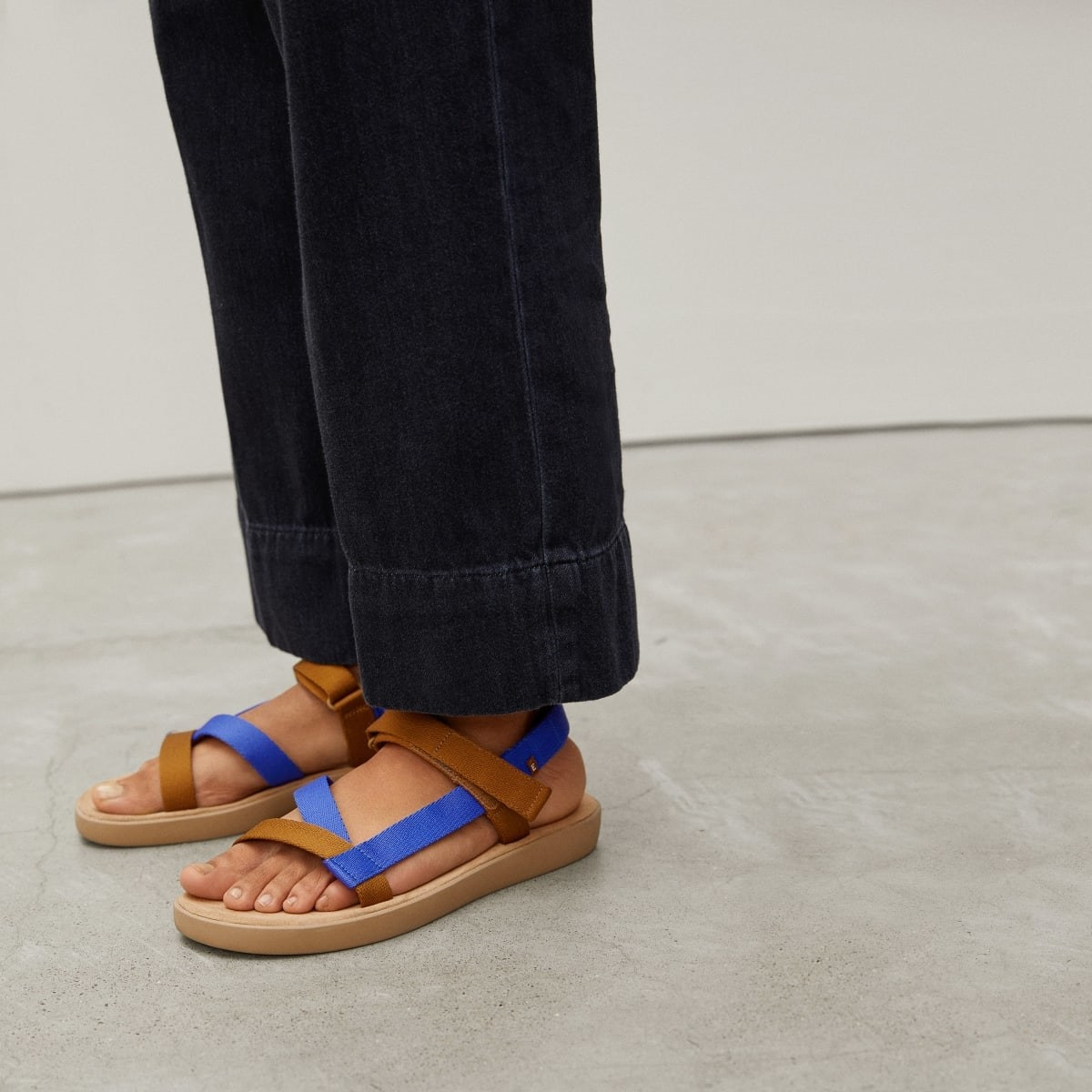 A model wearing the sandals in Brown/Blue
