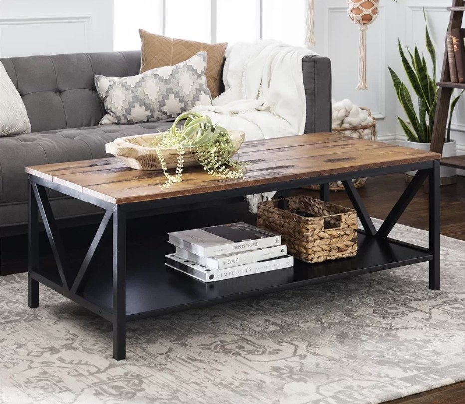 Wooden coffee table with black base and bottom shelf