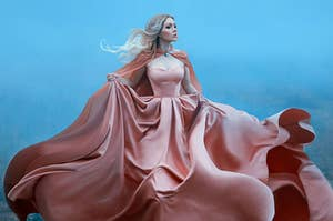 a woman in a flowing pink ballgown with matching cape