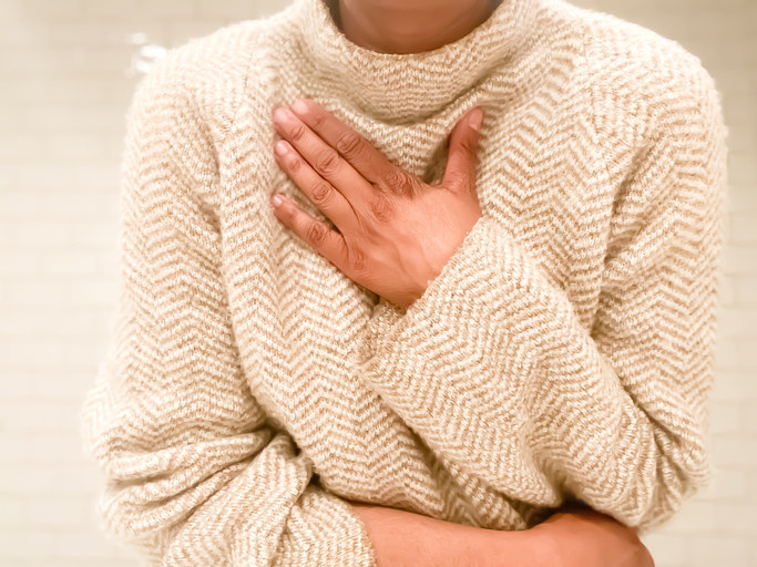 Woman in sweater clutching her chest