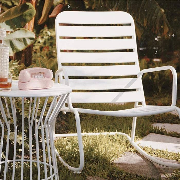 Low white piping rocking chair in grassy backyard