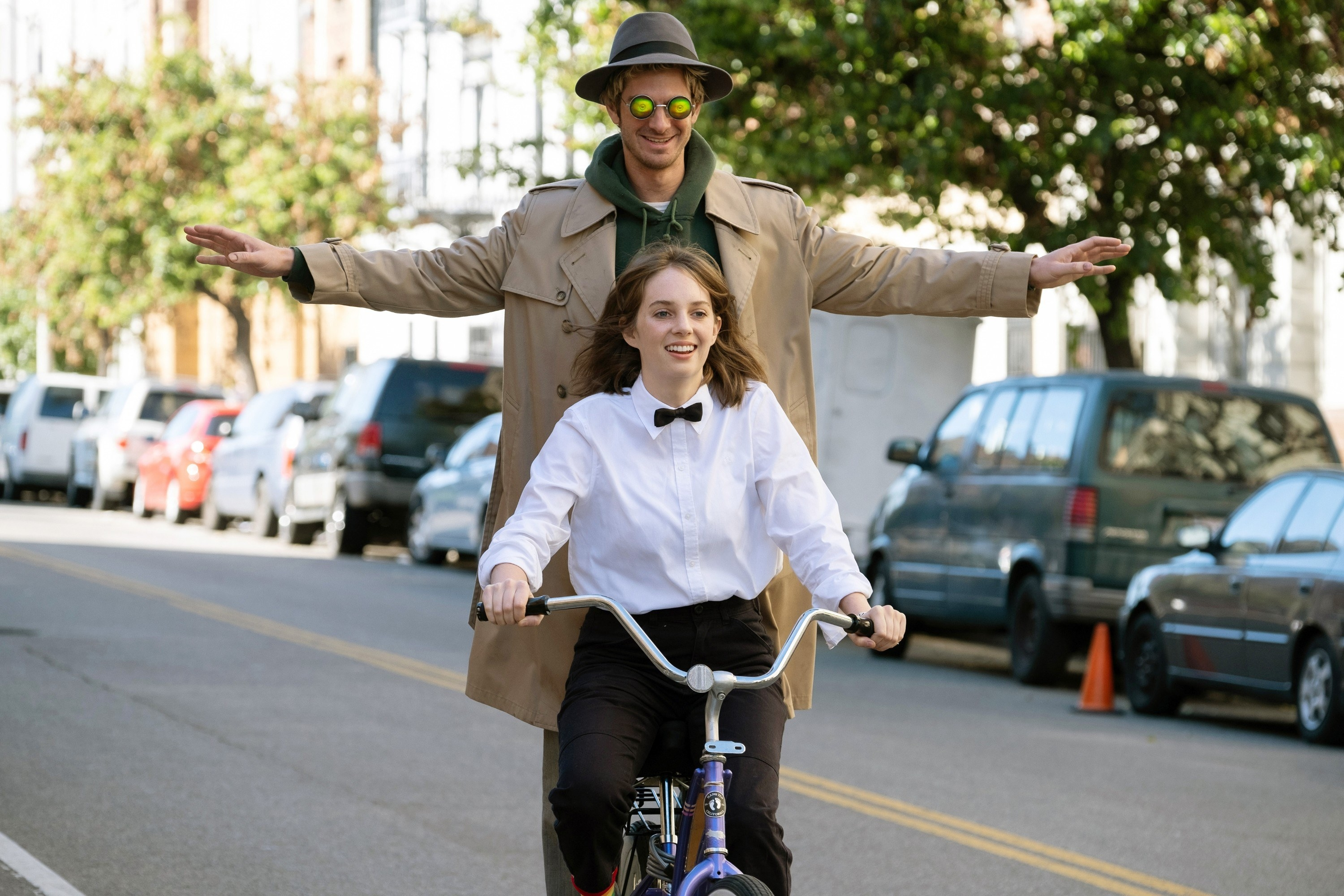 Andrew Garfield and Maya Hawke riding on a bicycle in the street