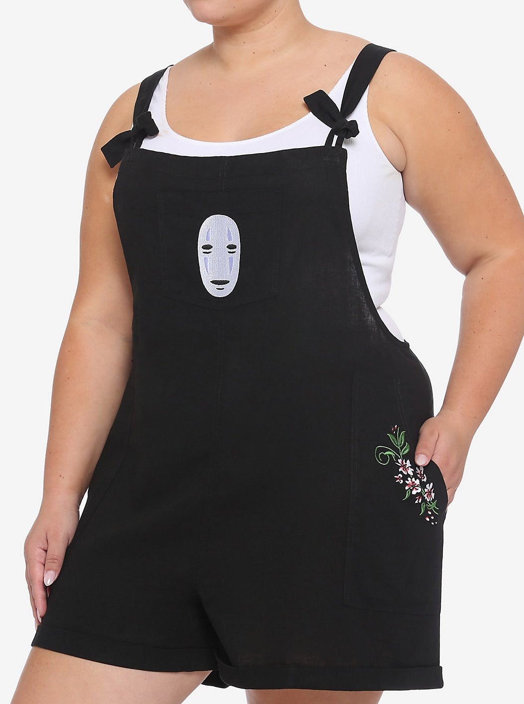 model wearing the black shortalls with embroidered No Face on the chest and floral embroidery on the pockets