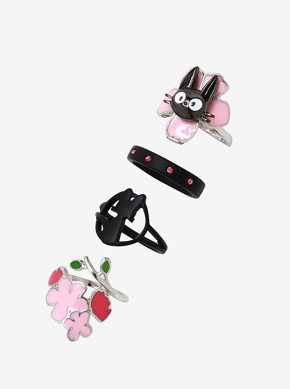silver ring with jiji's face on a pink flower, black band with pink rhinestones, black jiji silhouette ring, and silver and pink flower ring